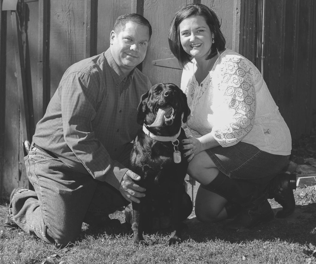Husband. Wife, professional photo, black lab, tongue out, black and white photo